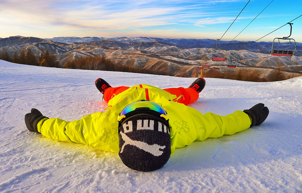Snowboarder_Laying_On_Snow_With_MountainRange_In_Background
